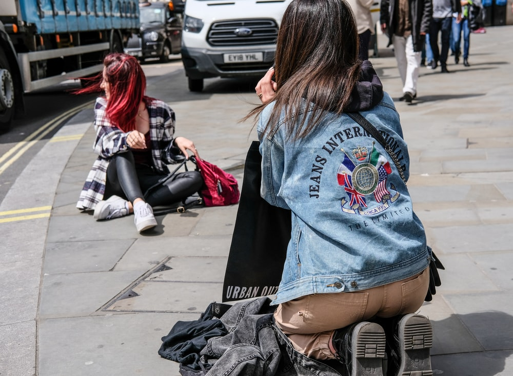 woman taking picture of woman sitting on sidewalk