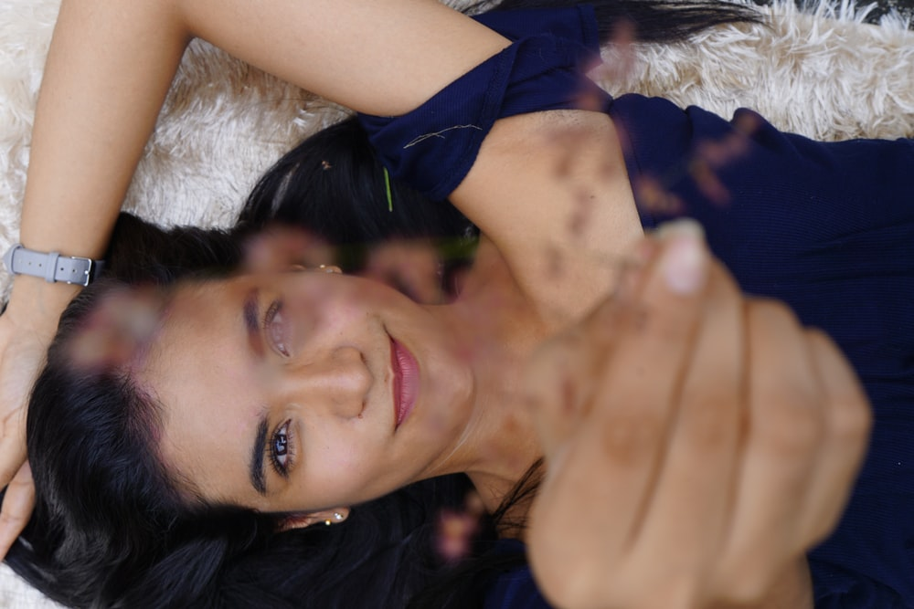 smiling woman in blue scoop neck dress lying on white rug