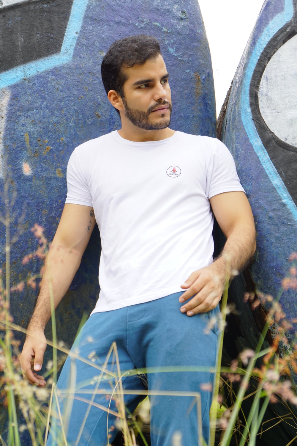 man in white crew neck t-shirt and blue pants leaning on blue and black painted rock