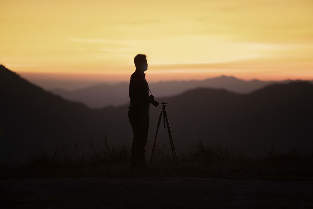 man standing beside camera tripod