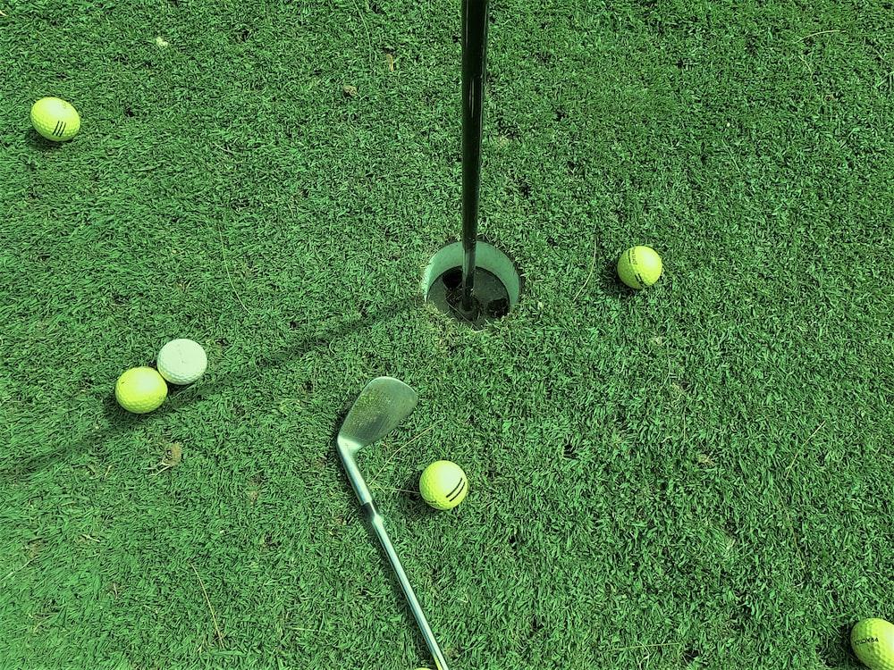 six golf balls near hole and one golf club
