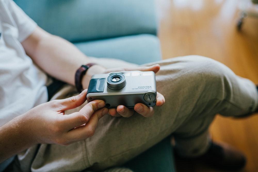 person holding grey SLR camera