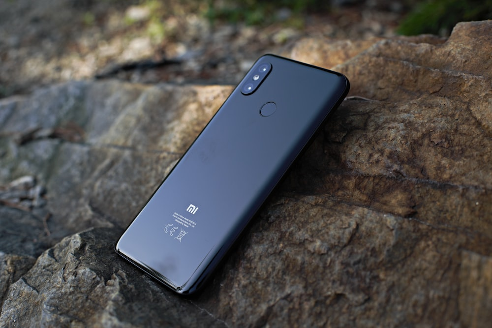 black Xiaomi Android smartphone on rock