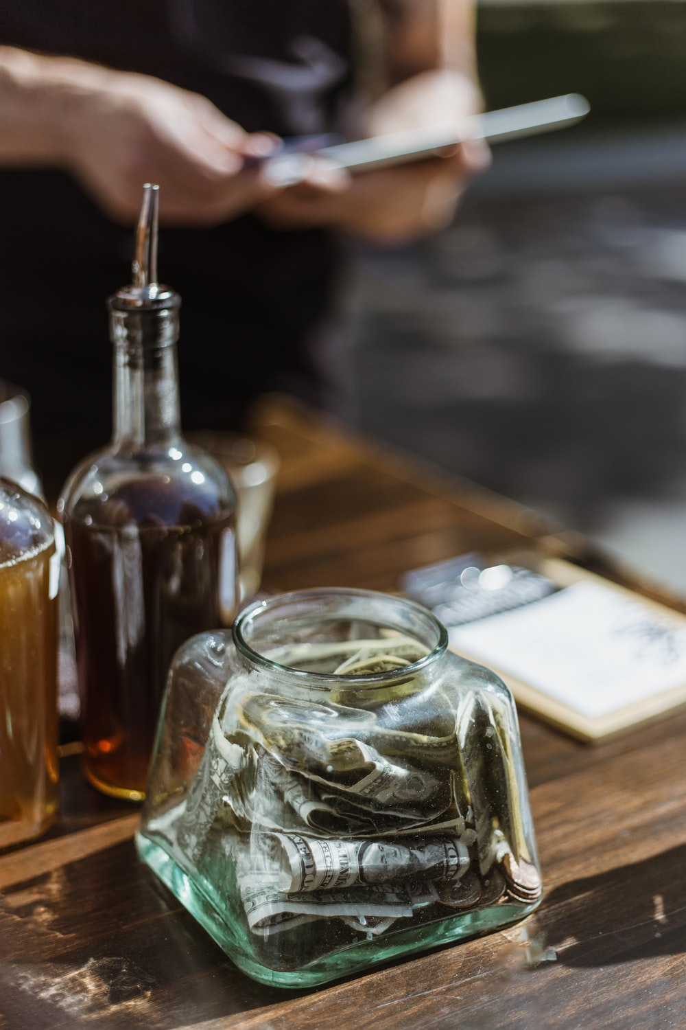 banknotes in clear glass container on wooden surface