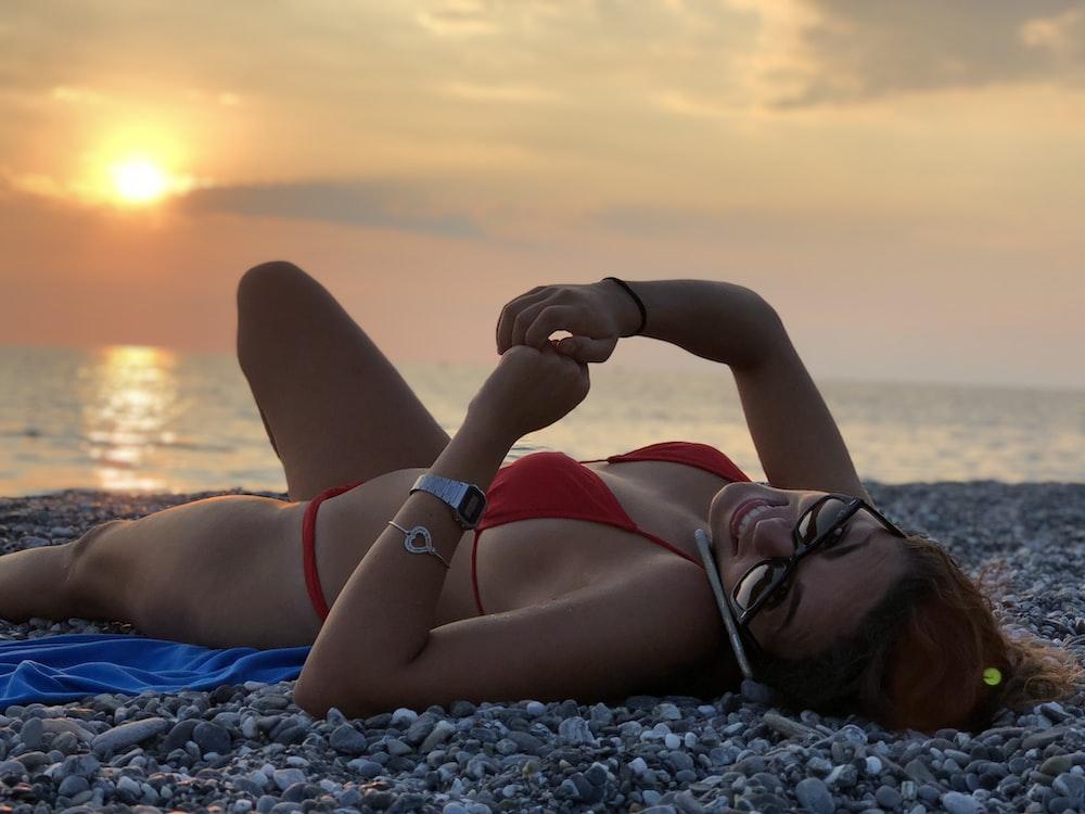 woman in red bikini lying on rocks while using phone