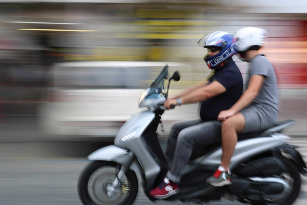 two men riding gray motor scooter