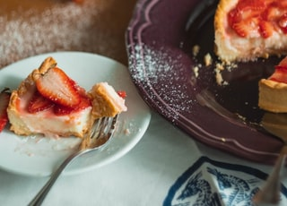 strawberry pie slice on saucer beside plate plate with pie
