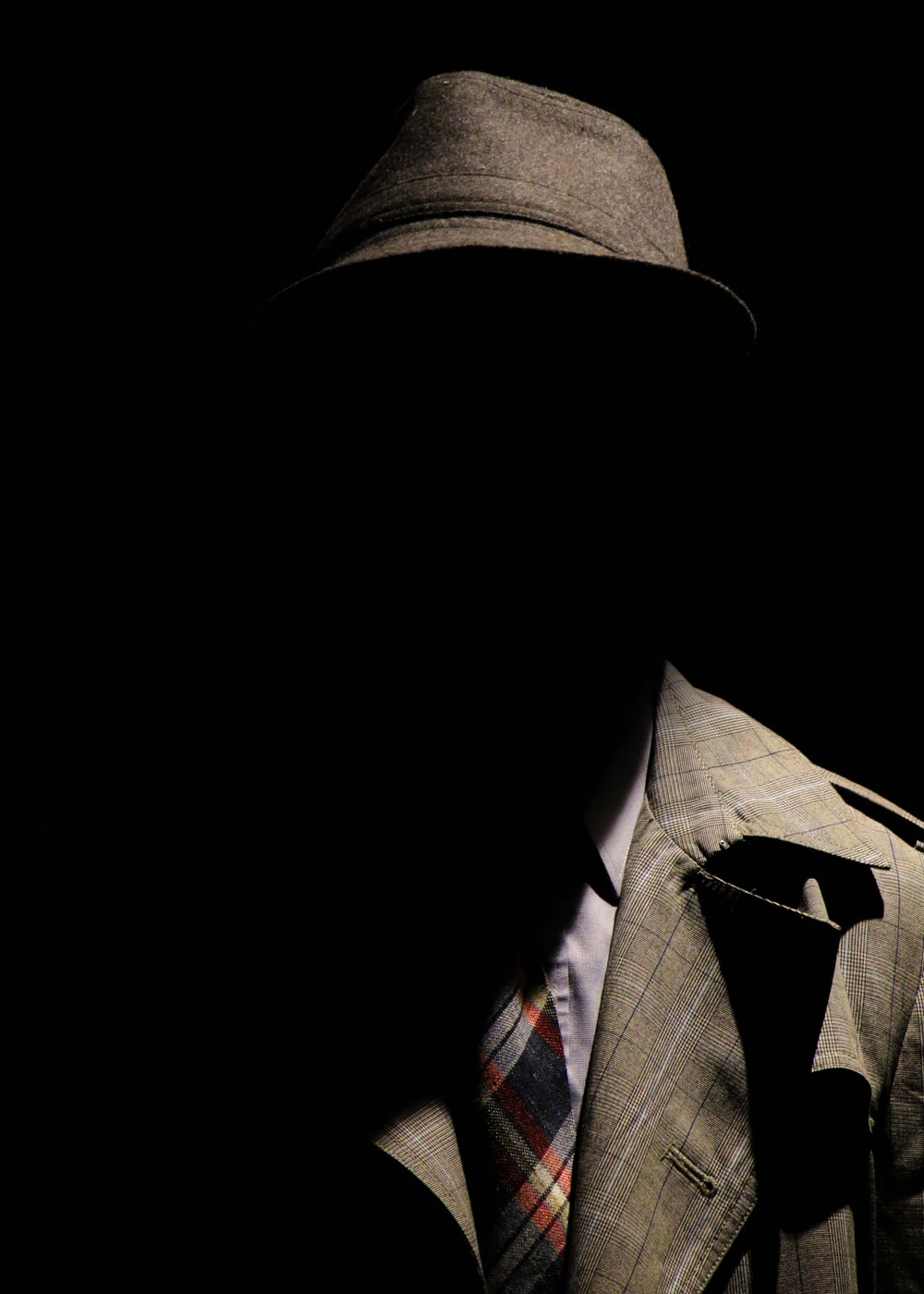 person wearing gray plaid notched lapel suit jacket and gray hat hiding face
