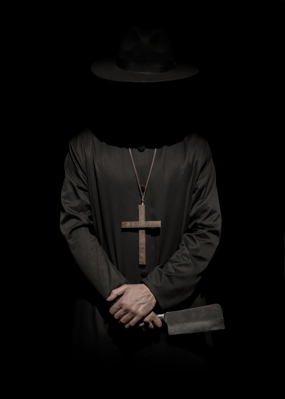 standing person wearing hat and cross necklace holding cleaver