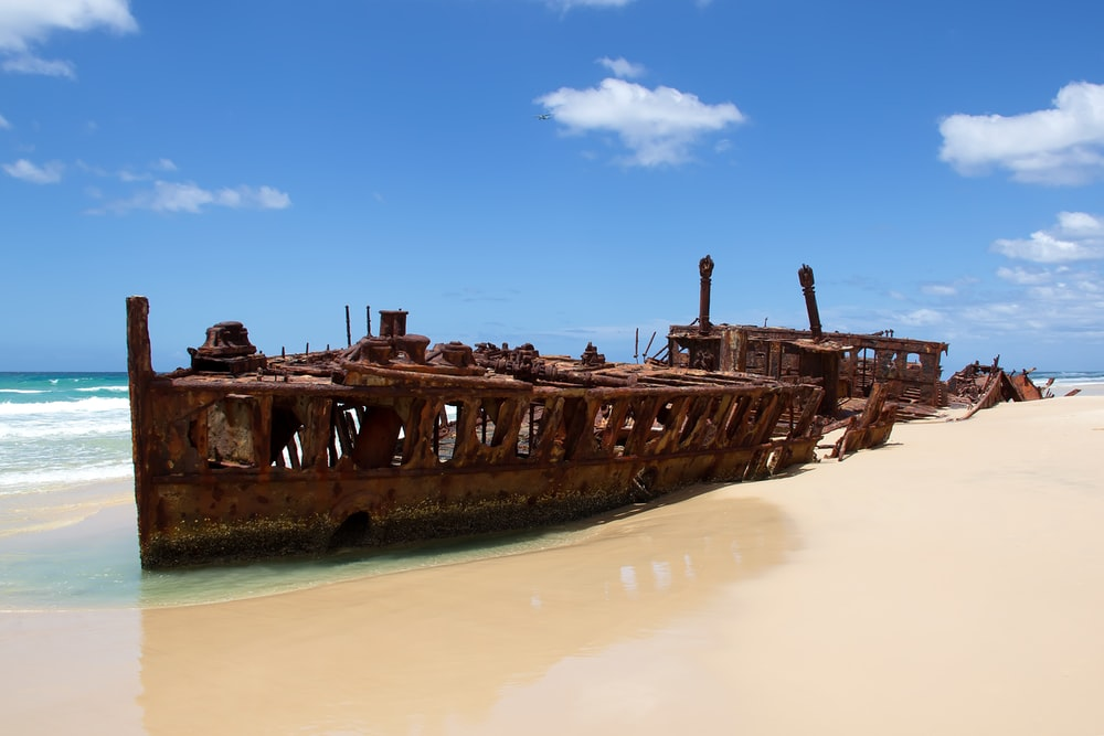 destroyed brown sailing boat near seashore under blue and white skies