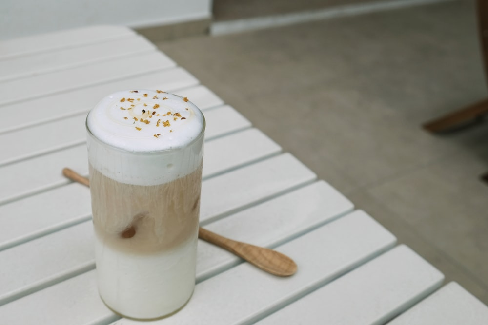 milk drink on glass beside wooden spoon