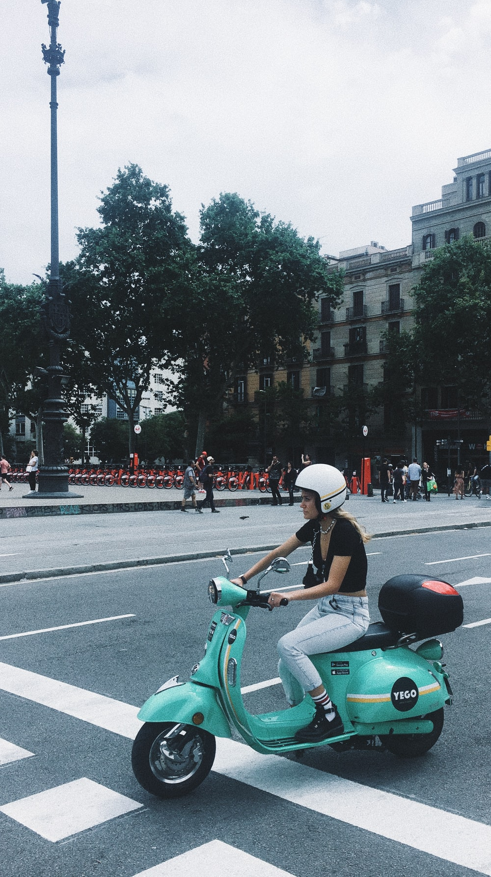 woman riding green motor scooter near road viewing people and buildings under white skies