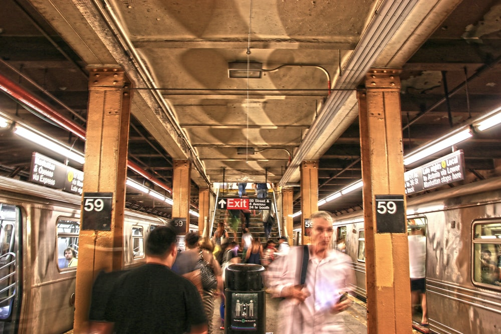 panning photo of people walking beside trains