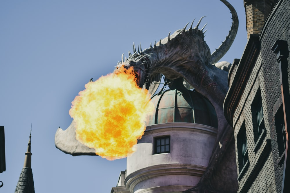 fire breathing dragon figure on building rooftop