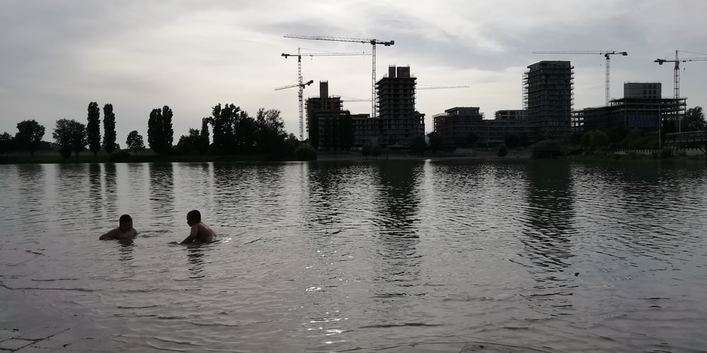 two person swimming on sea viewing city with high-rise buildings