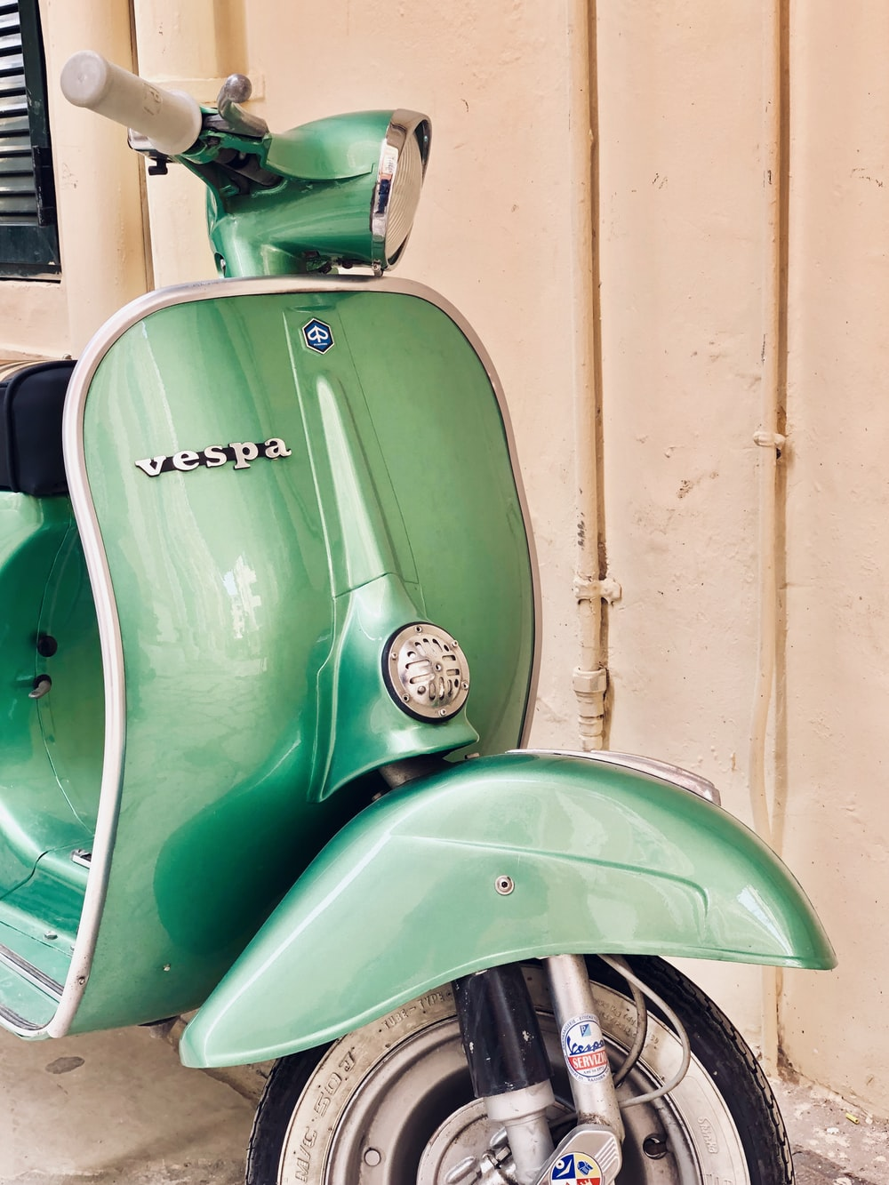 green and white Vespa motor scooter near white wall