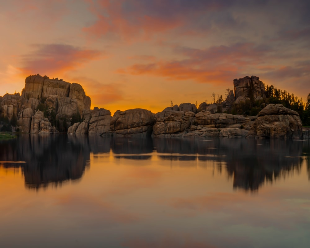 reflection of cliff on body of water during golden hour