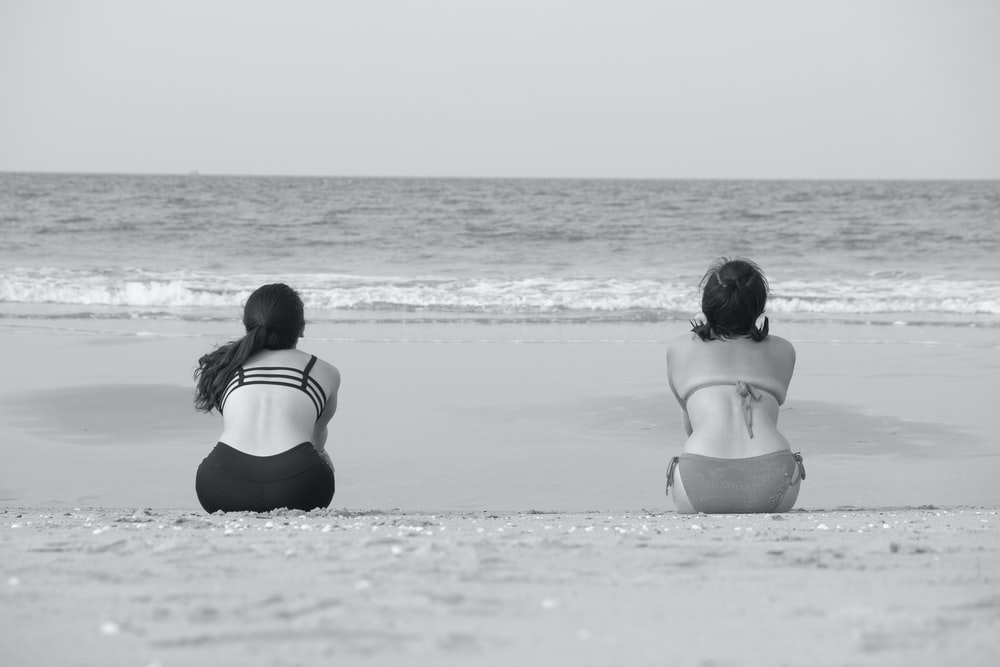 two women sitting on shore front of calm sea