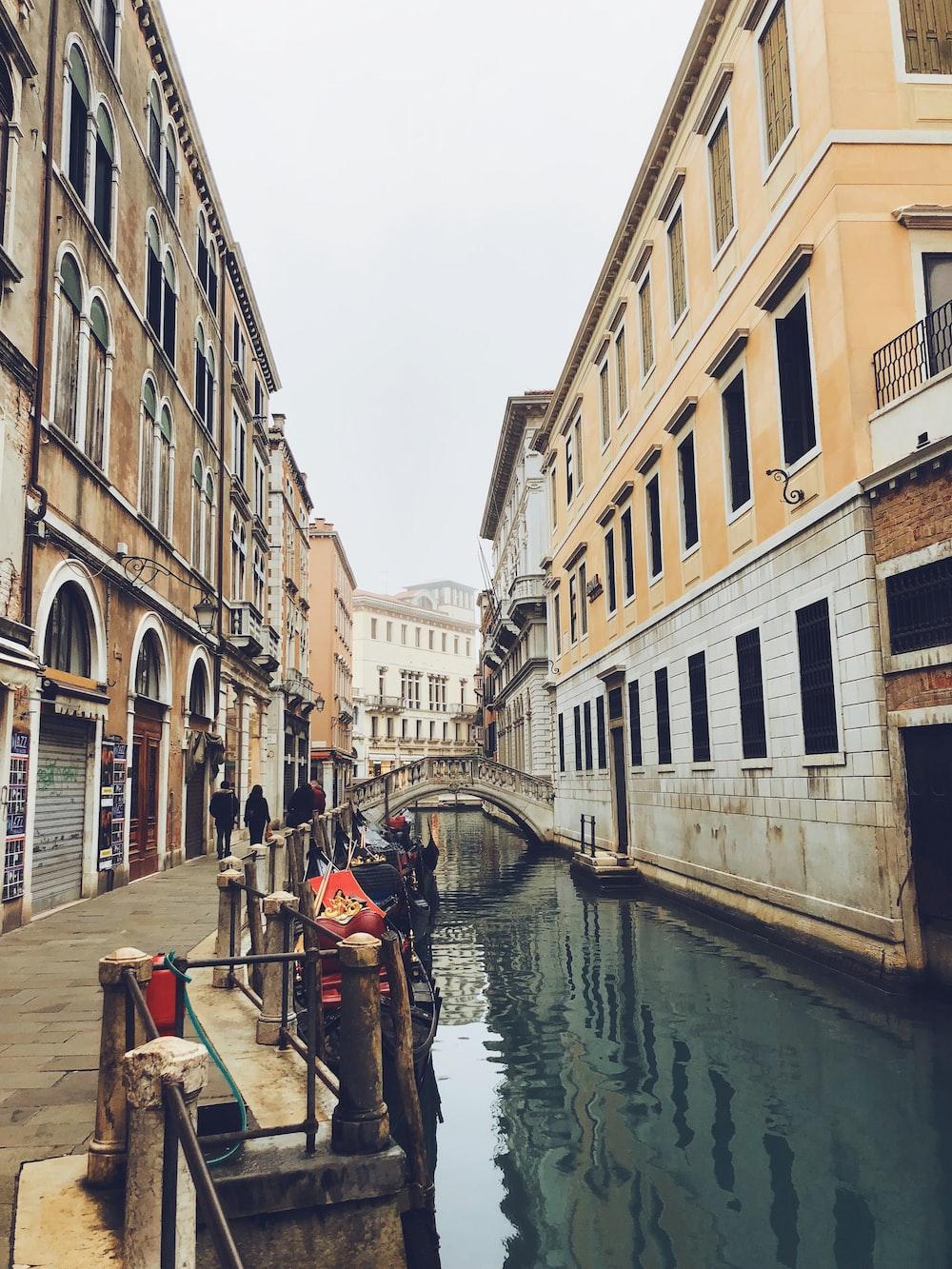 people walking in sidewalk beside canal