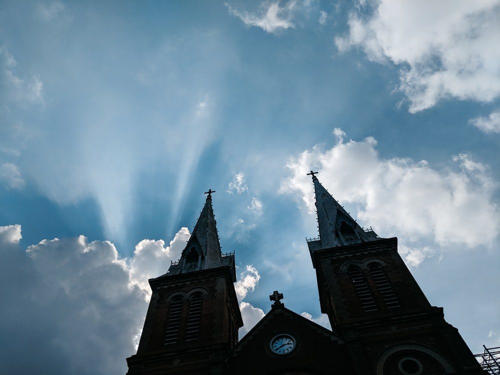 low-angle photo silhouette of cathedral under blue sky