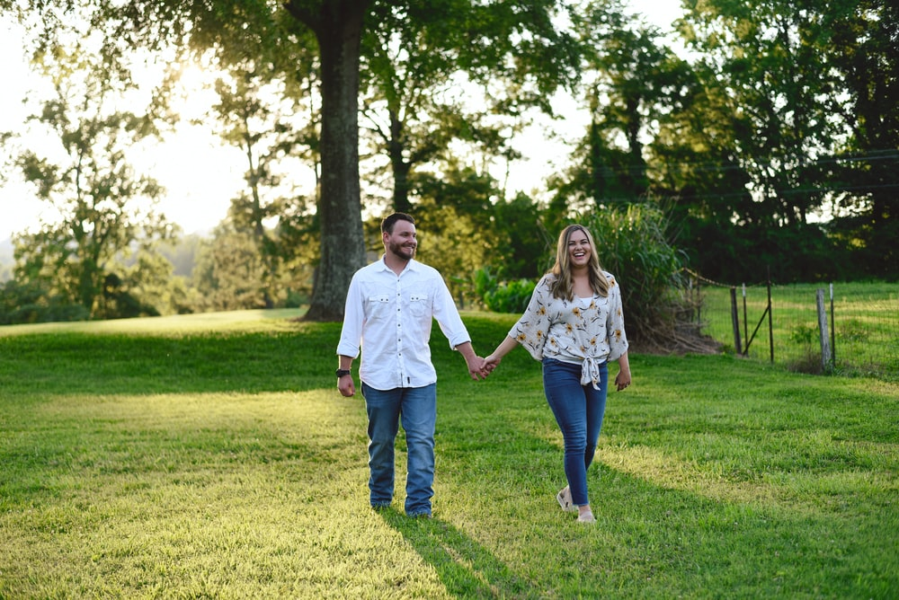 couple walking at grass lawn away from tree