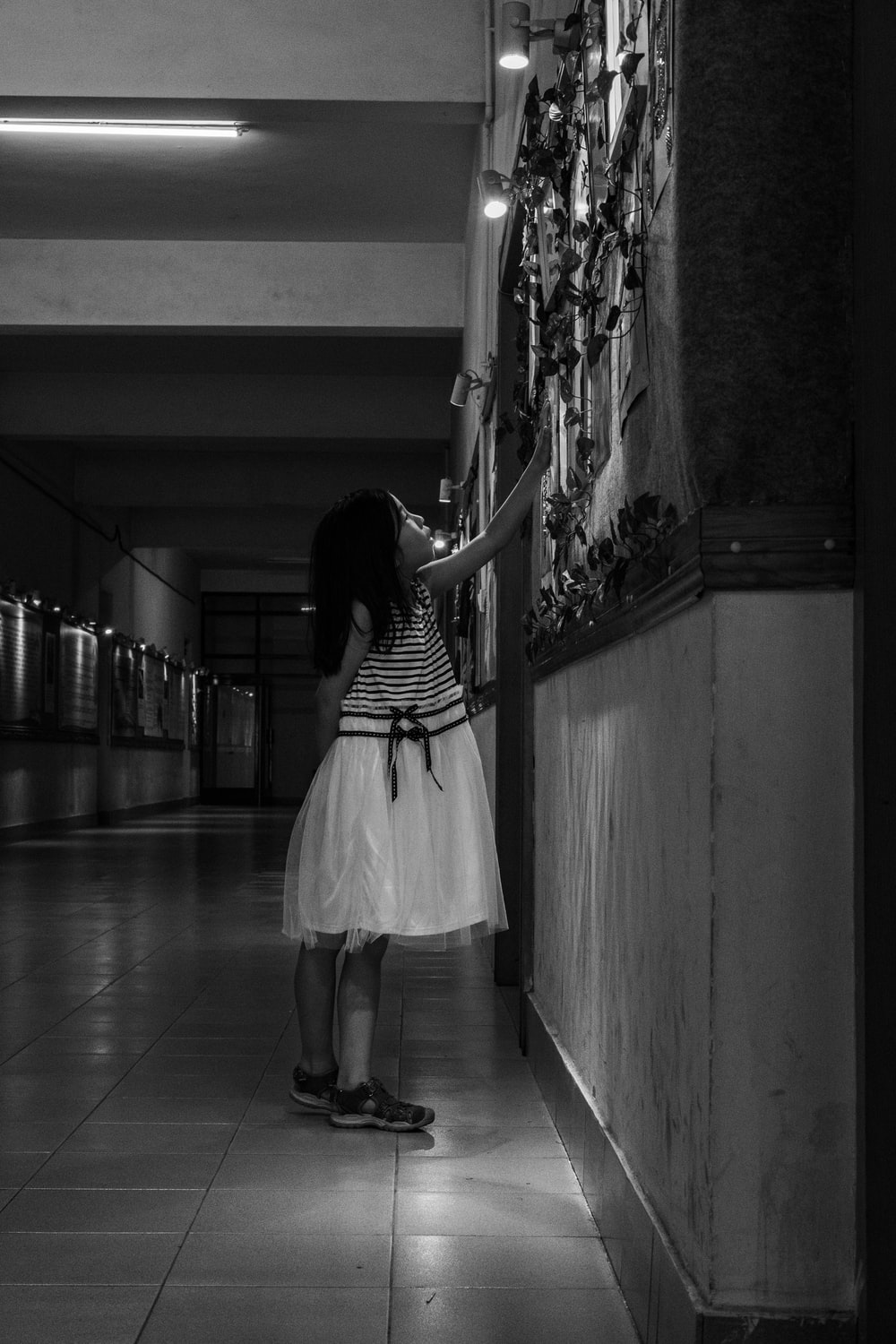 grayscale photo of girl standing by wall