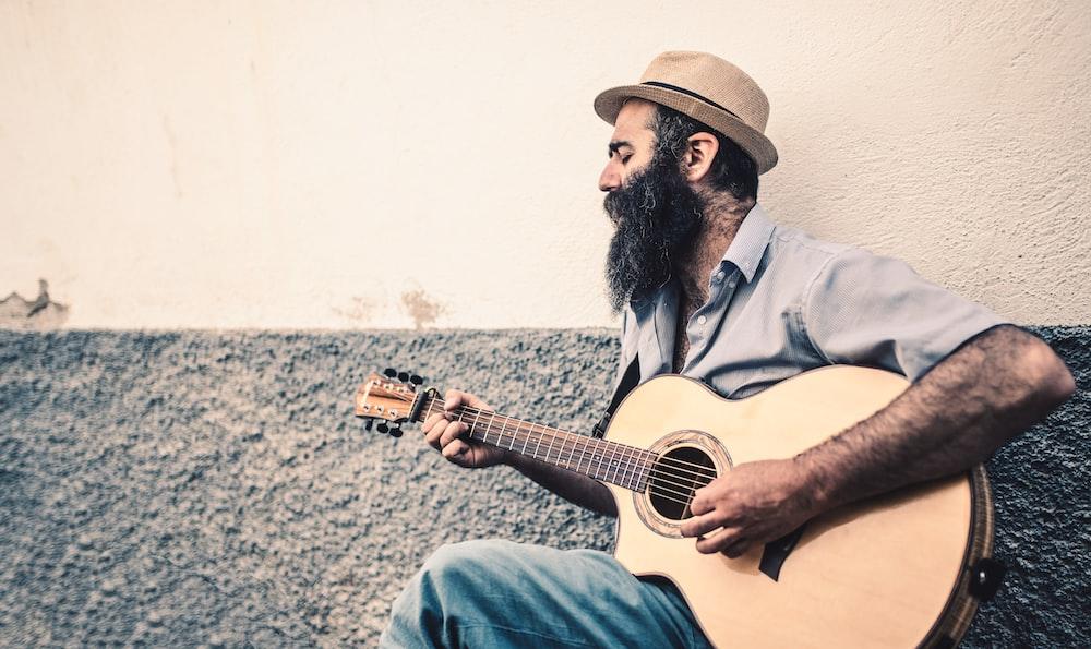 man in grey collared shirt-sleeved shirt playing guitar