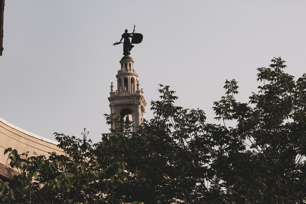 statue above concrete tower during daytime