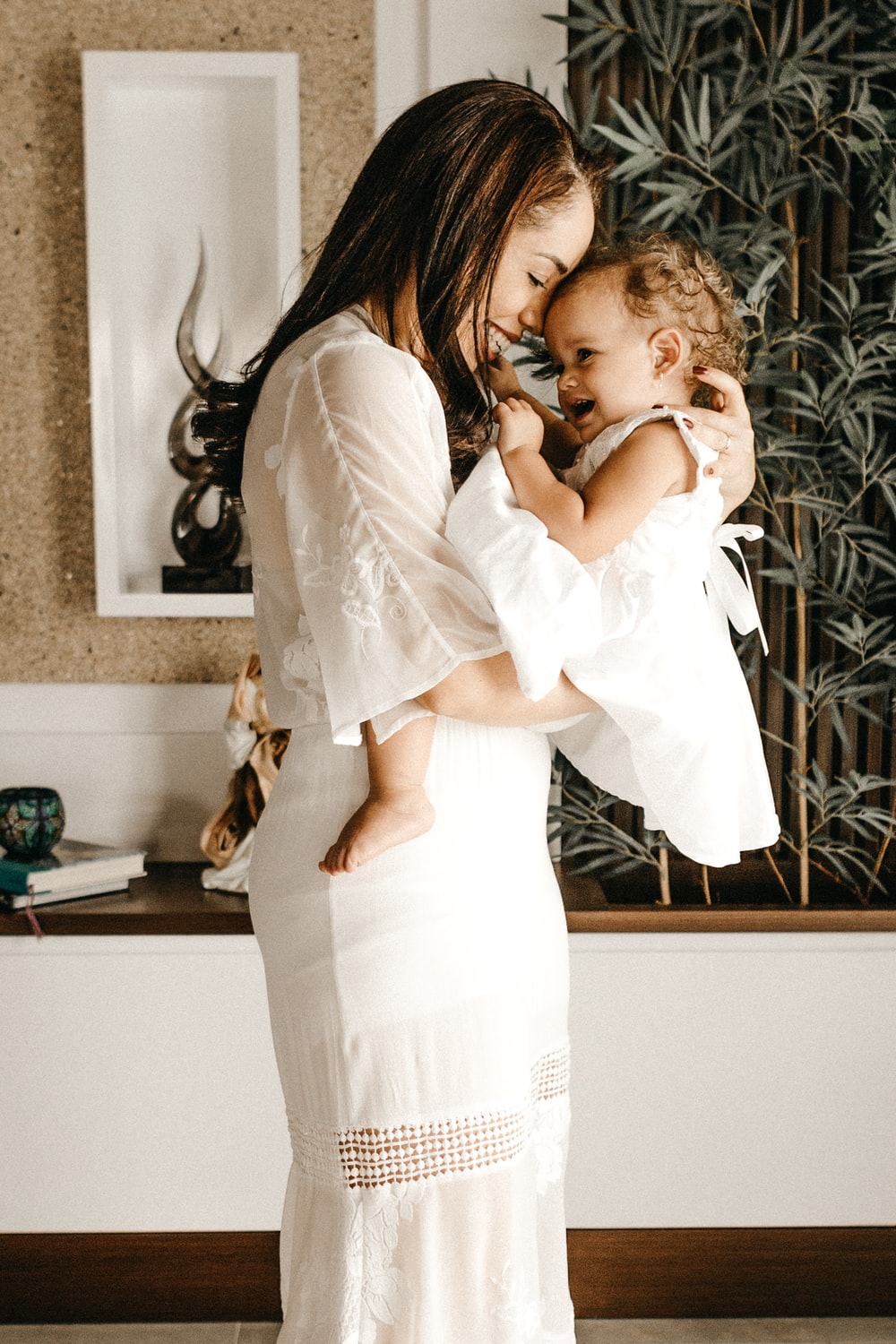 smiling woman in white dress holding toddler