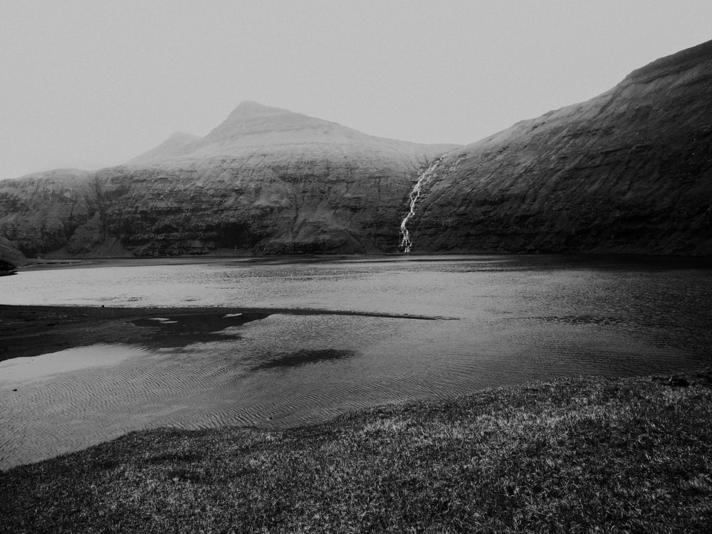 grayscale photography of lake near mountain