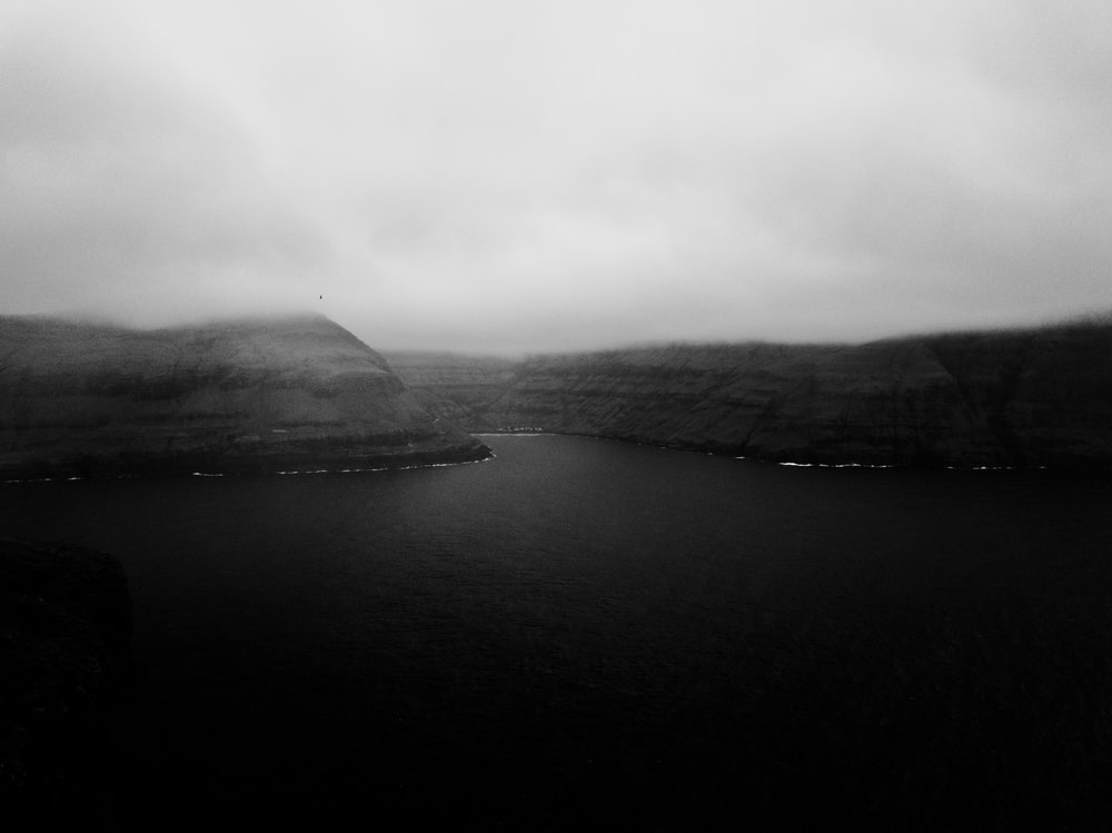 grayscale photography of river near mountain