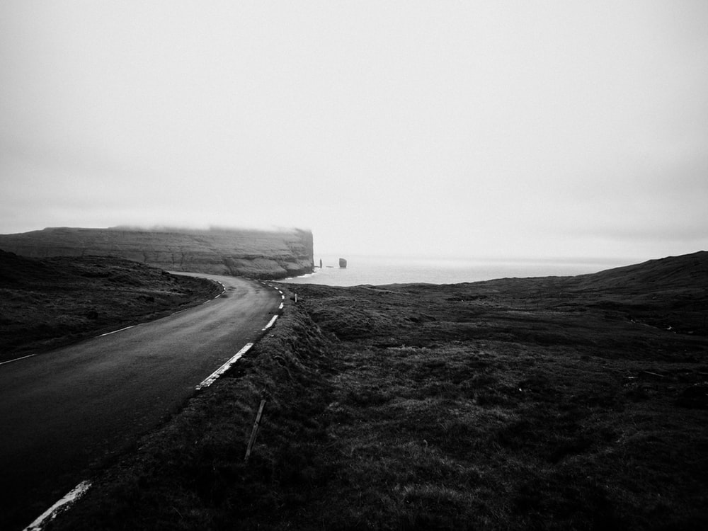 grayscale photography of curved road near body of water during daytime