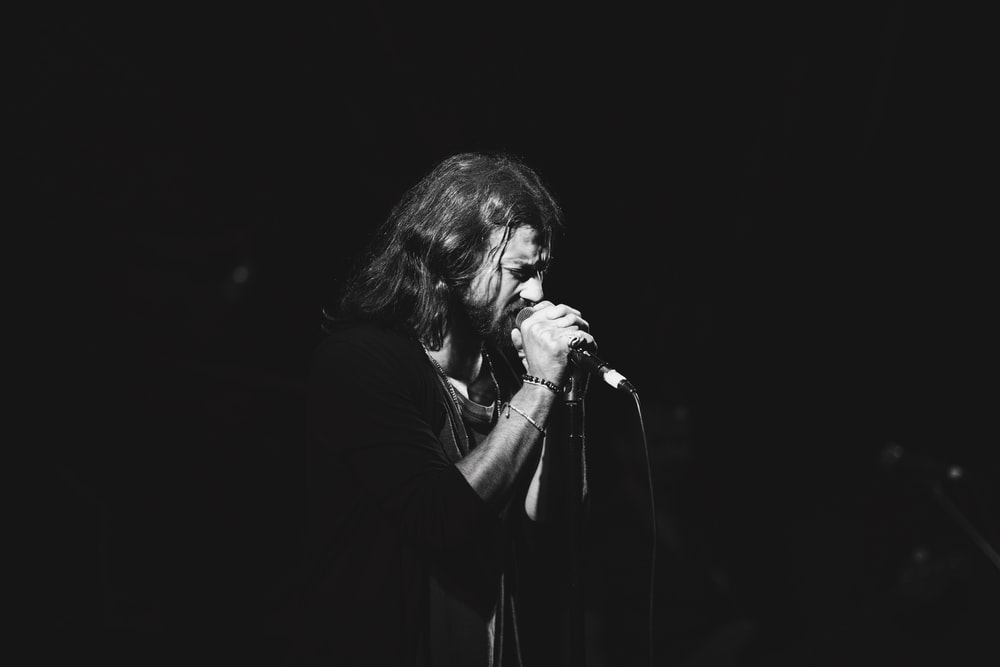 man using microphone in dark surface