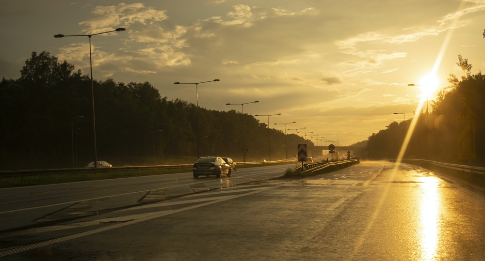 cars running on road during golden hour