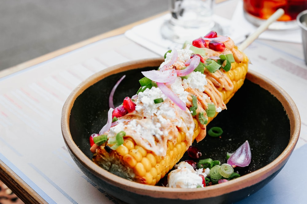 corn cob with stick on bowl