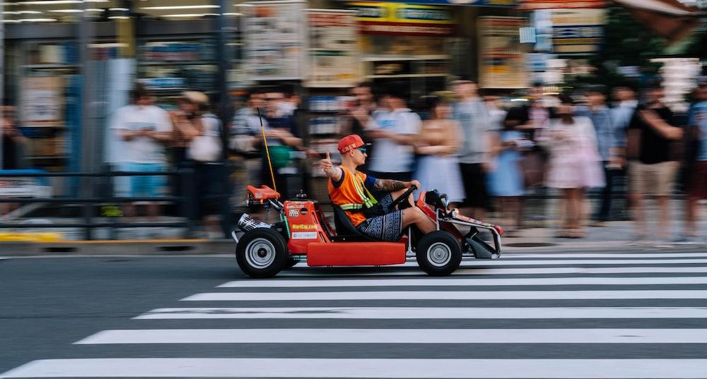 man riding go cart on pedestal lane near people watching