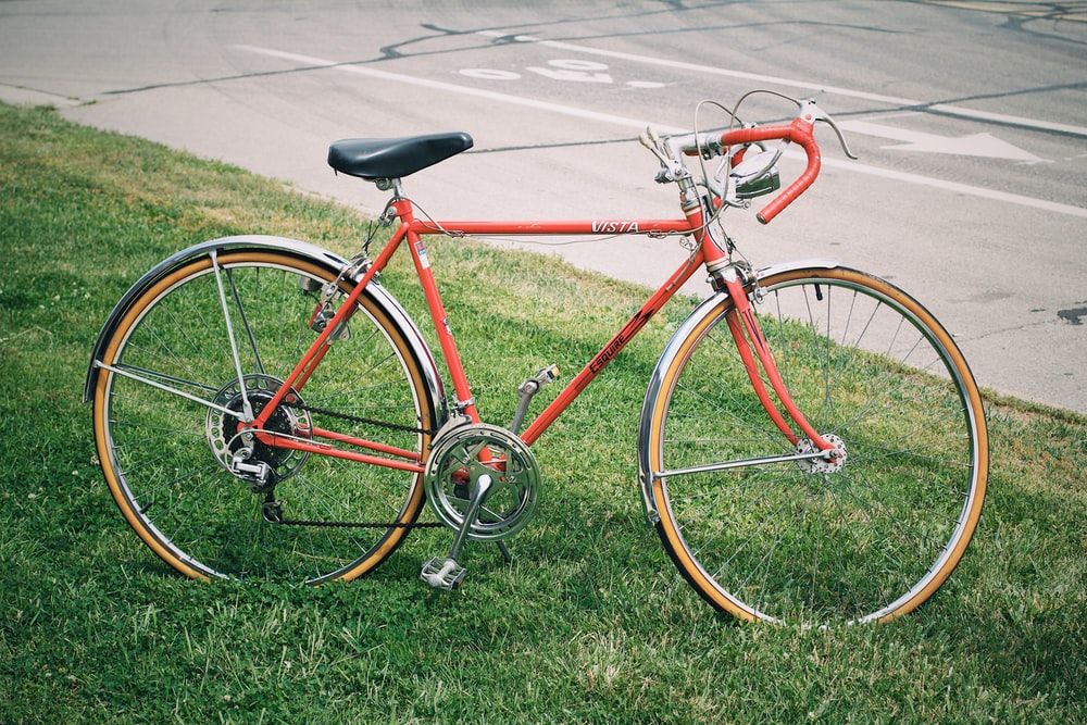 red road bike parked on grass
