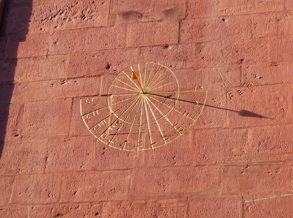 brown wall with carved sun clock