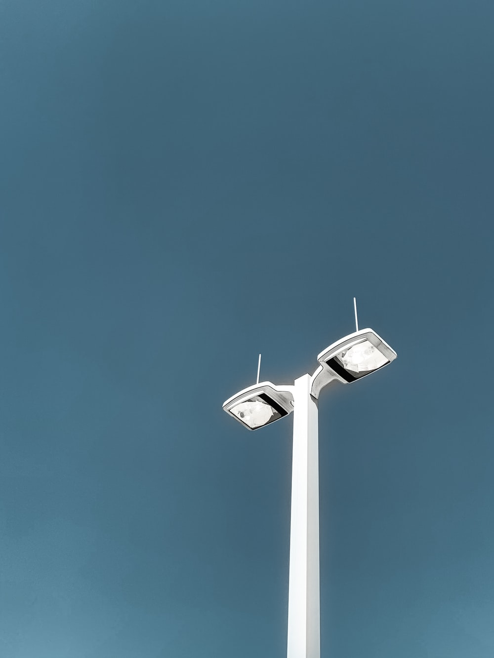 white 2-light lamppost during day