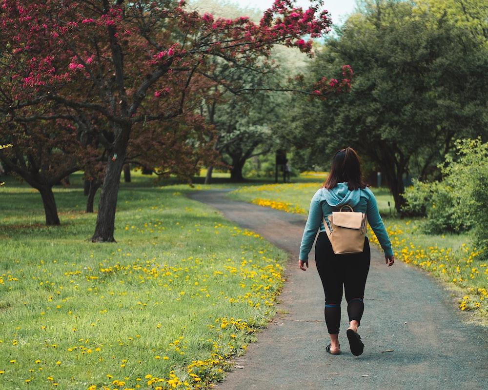 woman wearing blue jacket and black pants walking on grass field pathway