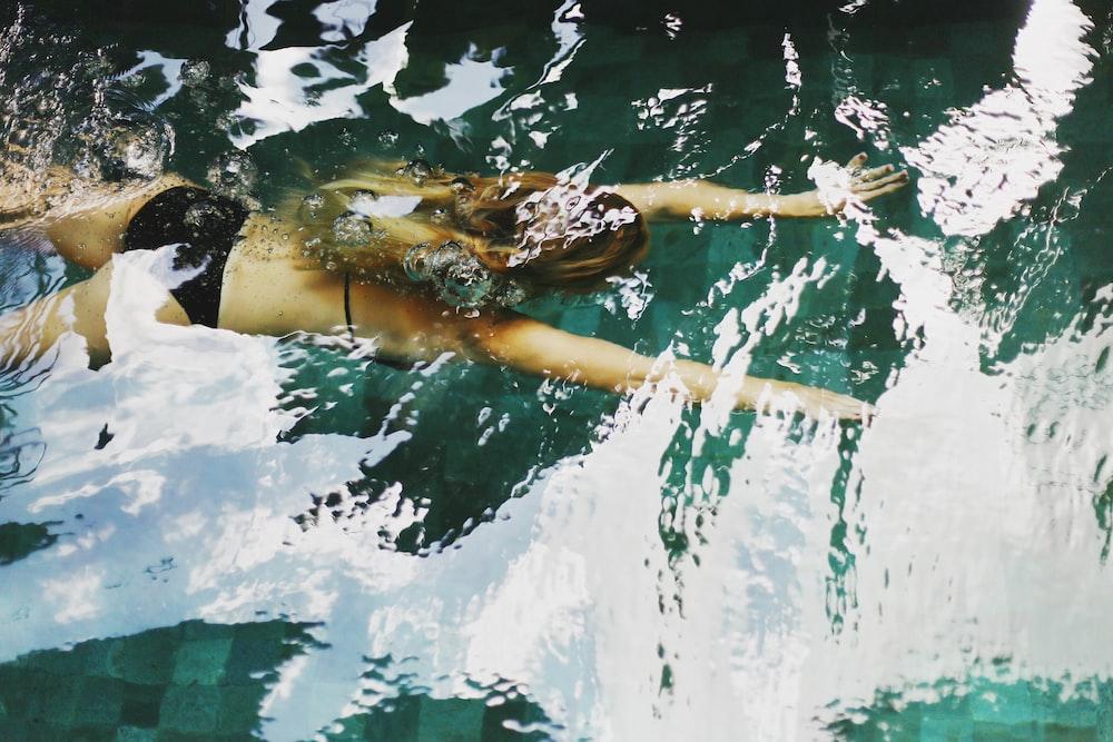 woman in black bikini swimming