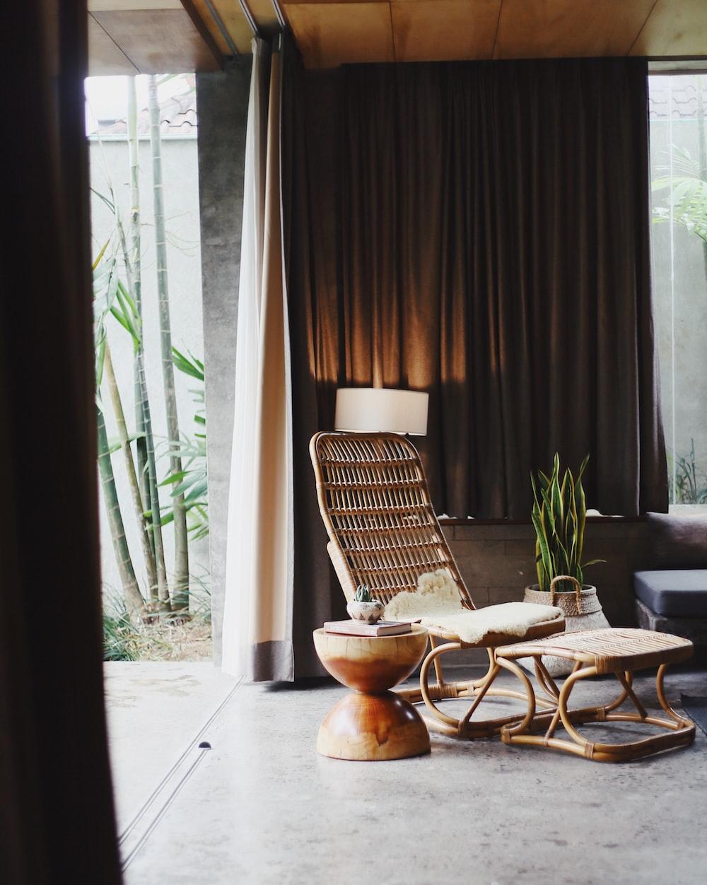 brown rattan chair with ottoman inside room near curtain