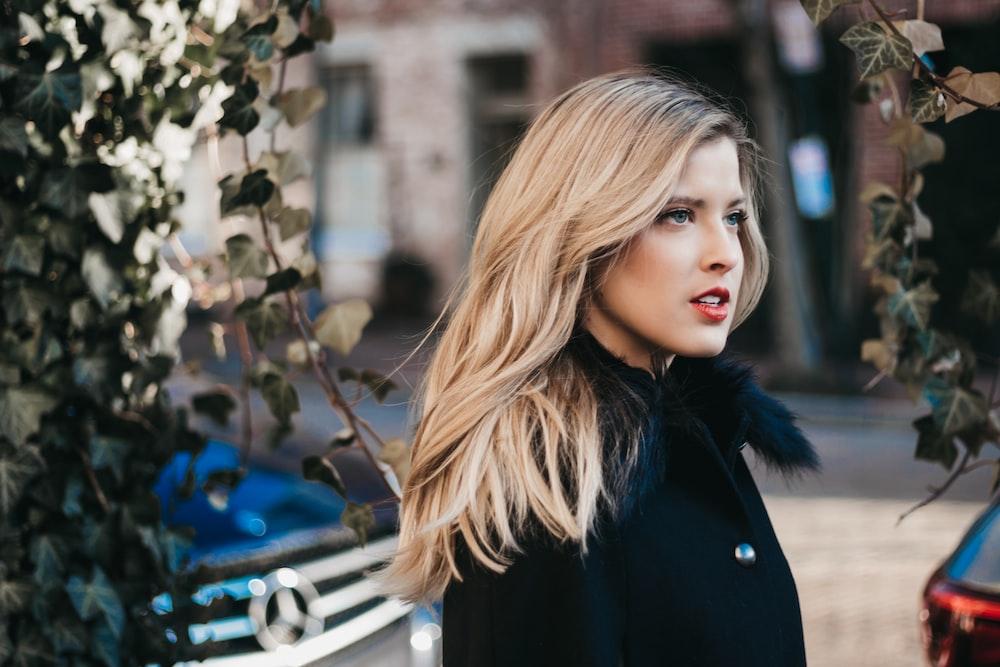 woman wearing black coat besides green vines photo