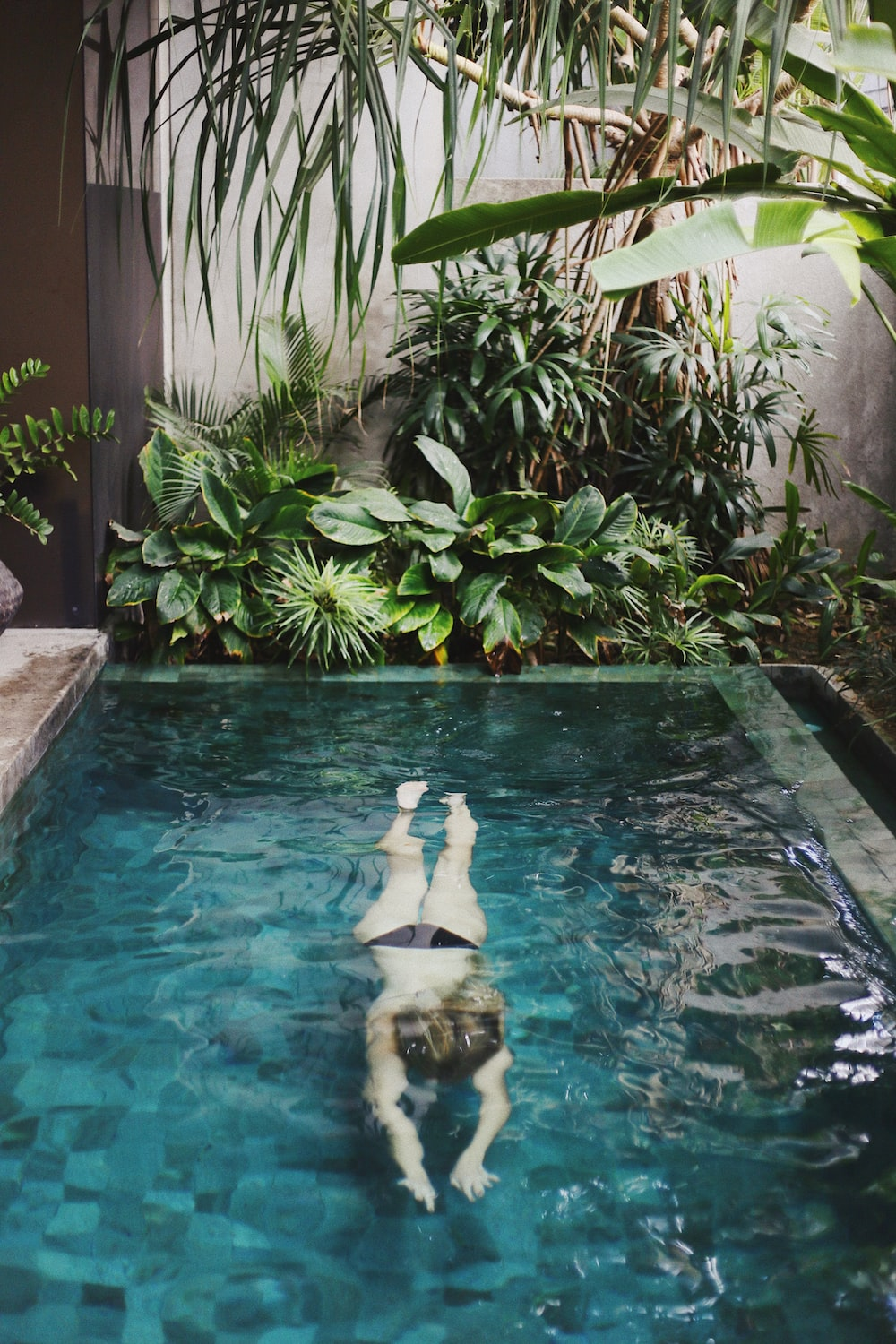 child swimming in pool near leaves