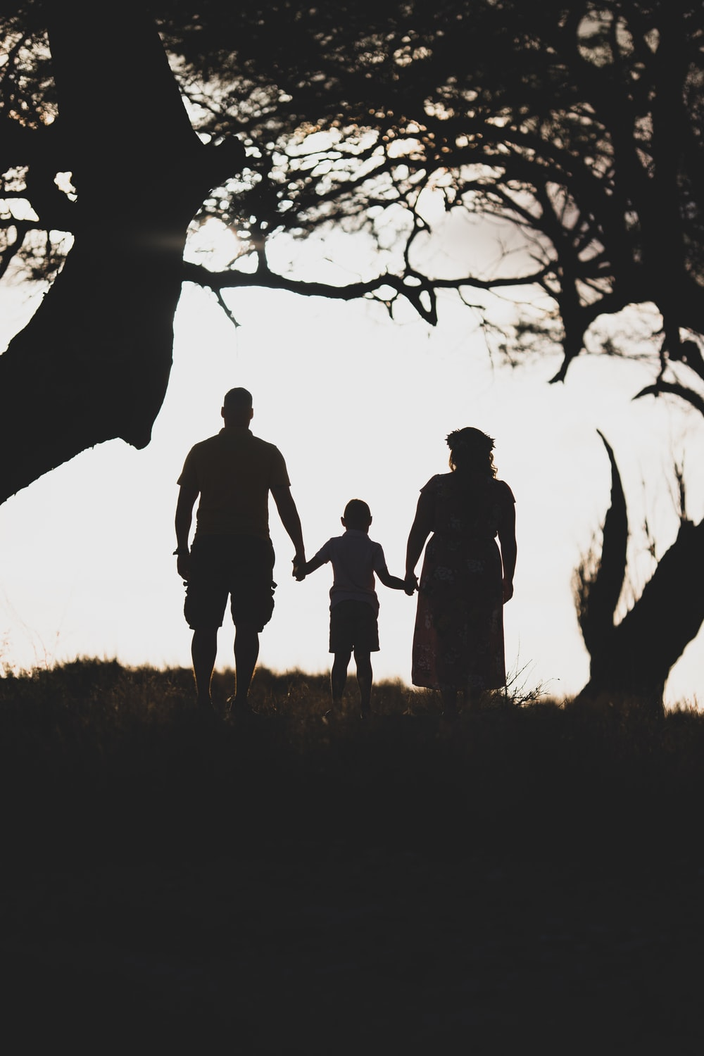three person standing in between of two tress during daytime grey-scale photography
