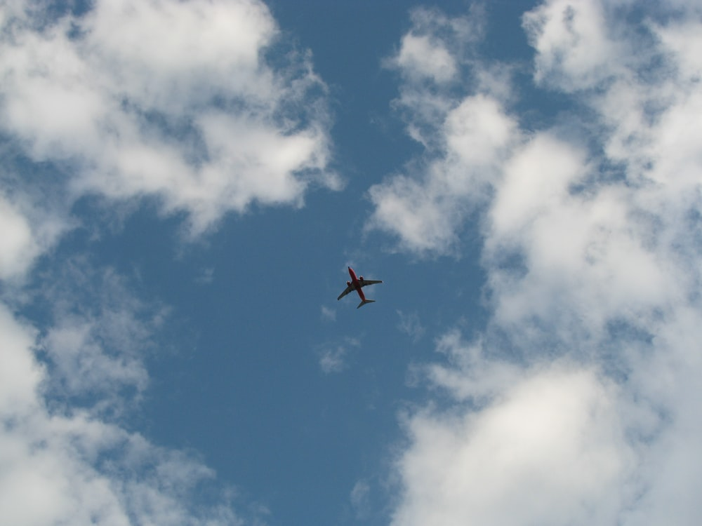 black and red airplane under blue and white skies