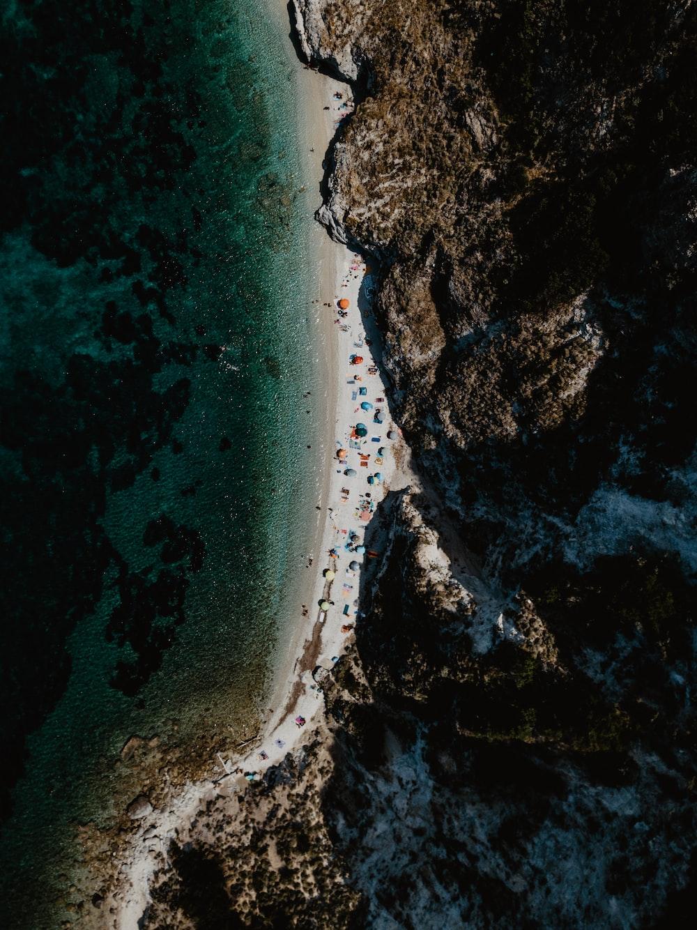 people near seashore viewing mountain