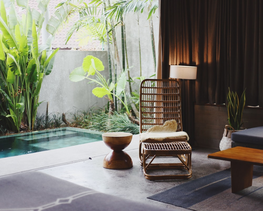 brown wooden chair and stool beside swimming pool