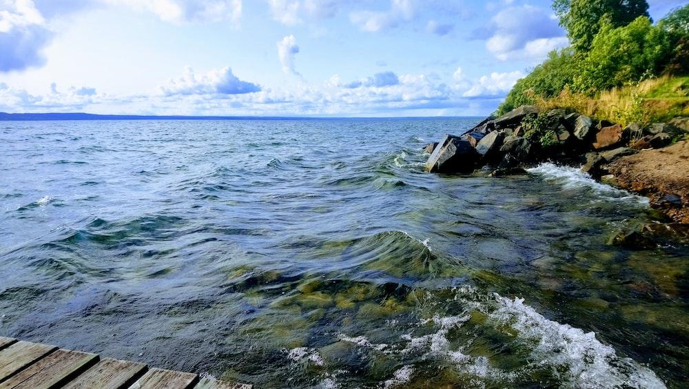 sea waves beside inside under clear blue sky