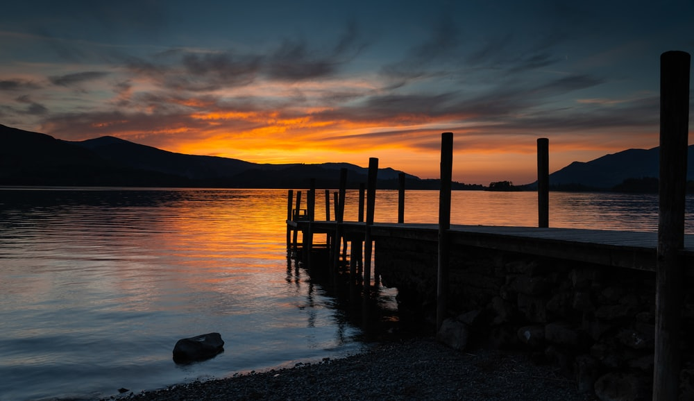 silhouette photography of dock in lake